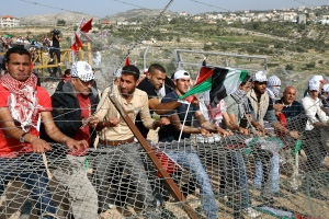 Palestinian and Israeli protesters try to break down a section of Israel's West Bank security fence during a demonstration near Bil'in, Feb. 19, 2010.