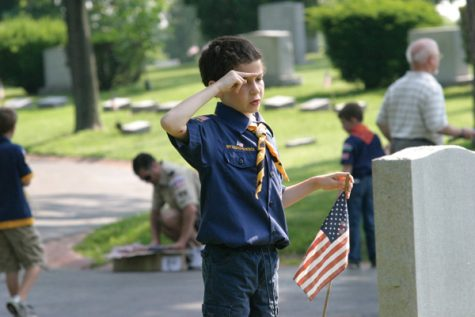 Andy Mesnier salutes after placing a new American flag at the grave of a veteran at New Mount Sinai Cemetery on Sunday morning. Mesnier, of Troop 982, based at Sorrento Springs Elementary School in Ballwin, was one of close to 100 Boy Scouts who came to the cemetery to place flags. Boy Scouts from Troop 11, based at Temple Israel also participated. About 275 scouts visited each Jewish cemetery on Sunday.