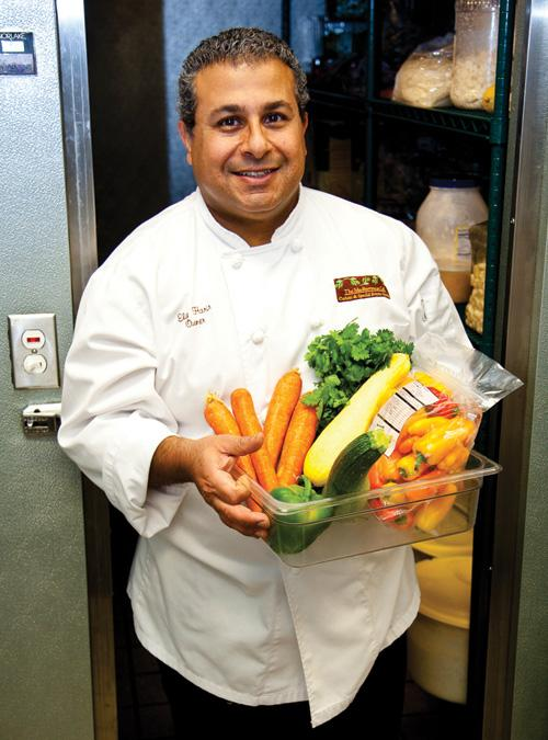 Chef and owner Elie Harir emerges from his walk-in refrigerator with fresh vegetables.