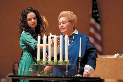 Survivor Sarah Klein (right) lights a candle with her granddaughter, Hannah Klein, during the 2010 Yom HaShoah community commemoration at Brith Sholom Kneseth Israel.  This year's Yom HaShoah takes place Sunday, May 1 at Congregation Shaare Emeth. File photo: Lisa Mandel