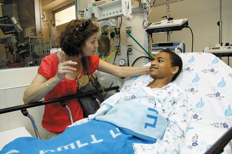 Laura Kafif, the house mother at Save A Childs Heart, visits with one of her charges, Zeresenay Gebru, as he recovers from heart surgery at Wolfson Medical Center in Holon, Israel on May 31. Photo: Sheila Shalhevet