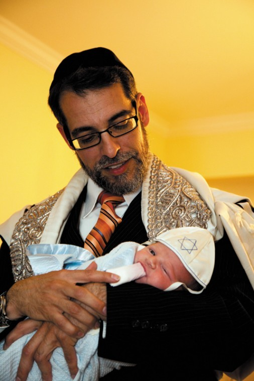 Rabbi and mohel Mike Rovinsky holds Benjamin Miller, son ofDr. Aaron and Nanci Miller,during a bris ceremony last week.
