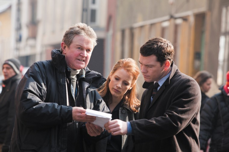 Director John Madden (left), Jessica Chastain (center) and Sam Worthington (right) on the set of The Debt. Photo: Laurie Sparham