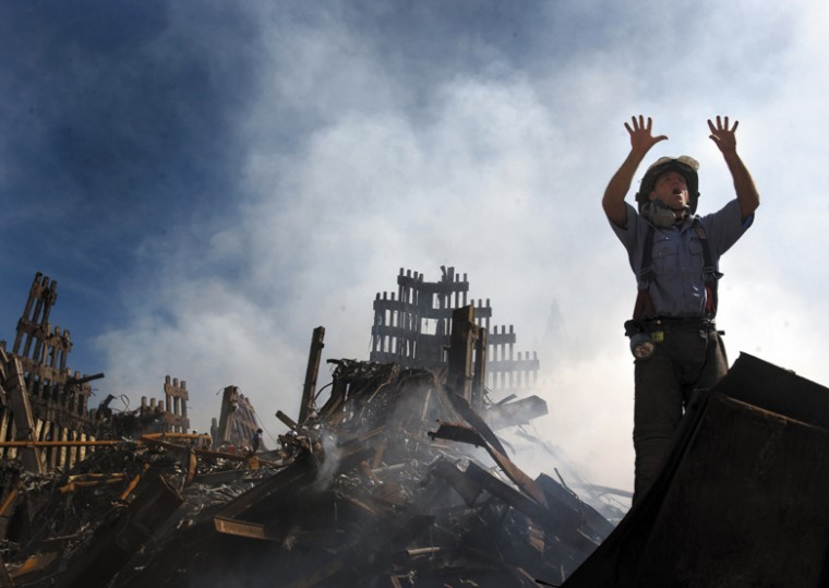 A New York City fireman calls for 10 more rescue workers to make their way into the rubble of the World Trade Center. U.S. Navy Photo by Journalist 1st Class Preston Keres.