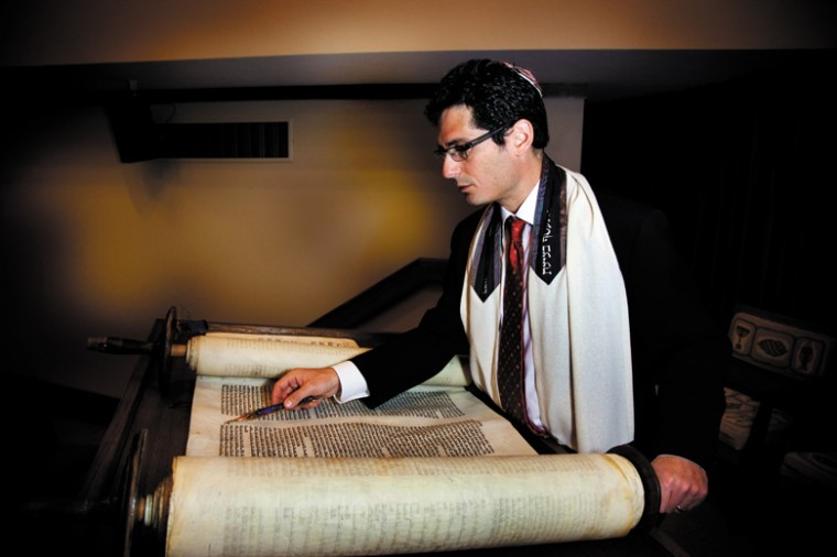 Temple Emanuels Rabbi Justin Kerber is pictured with Holocaust Memorial Scroll No 420. The congregation has welcomed the Torah, which used to be housed at Congregation Kol Am. Kol Am disbanded earlier this year. Photo: Kristi Foster