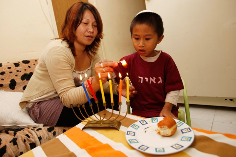 Filipinos light Chanukah candles in their home in South Tel Aviv on Nov. 24, 2010 in advance of the Jewish holiday.