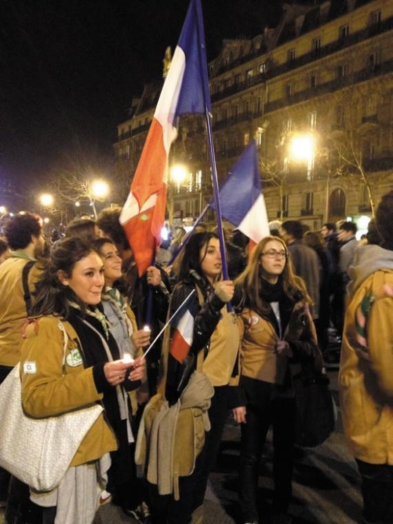 Women raising French flags during a silent demonstration in Paris to protest recent murders in France, March 20, 2012.