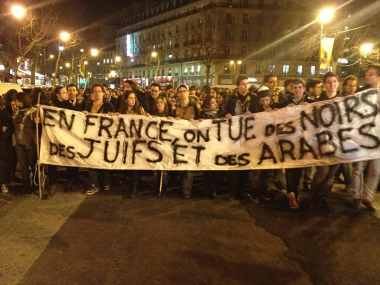 Protesters raising a banner reading in France, we kill Blacks, Jews, and Arabs during a silent demonstration in Paris, March 20, 2012.