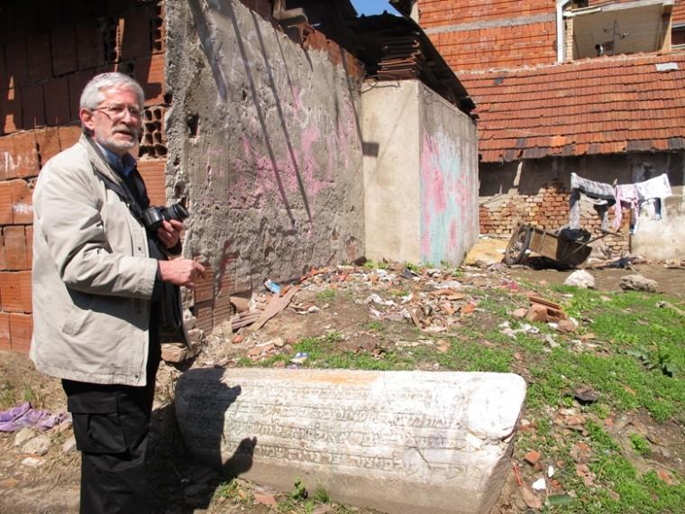 Ivan Ceresnjes of the Center for Jewish Art in Jerusalem at a Jewish tombstone that can been seen in the Roma village built on top of part of the Jewish cemetery in Nis.