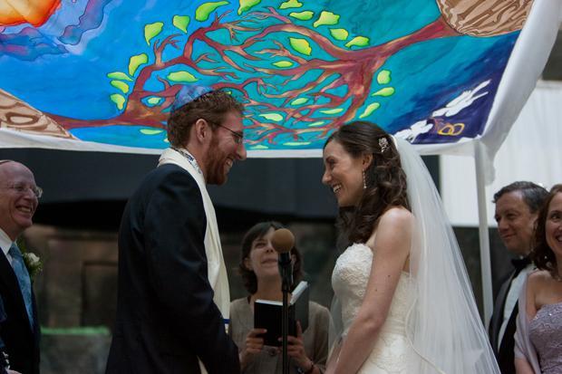 Jon+Citel+and+Ashley+Novack+standing+beneath+a+hand-painted+silk+chuppah+that+Novack%27s+sister+made+for+the+couple%27s+wedding.%0A