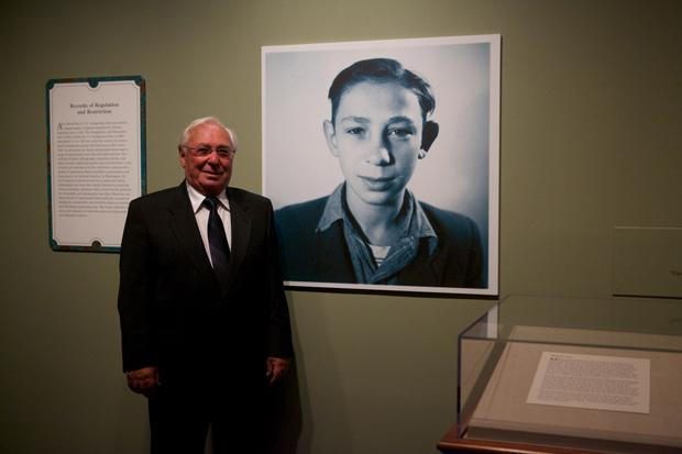 Holocaust+survivor+Michael+Pupa+standing+next+to+his+childhood+photo+in+the+Attachments+exhibit+at+the+National+Archives+in+Washington%2C+D.C.%0A