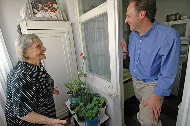 Claims Conference chief Greg Schneider visiting a Nazi victim at her home in Moldova.