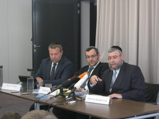 Left to right, speaking at a news conference in Berlin are Shimon Cohen, spokesman for the Conference of European Rabbis; Rabbi Avichai Apel, a board member of the German Orthodox Rabbis Conference; and Rabbi Pinchas Goldschmidt, president of the Conference of European Rabbis, July 12, 2012.