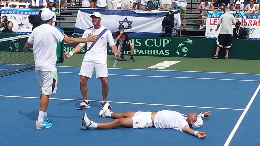 Israel's Andy Ram sprawled on the court following his five-set doubles victory with partner Yoni Erlich, holding racket, against Argentina in a Davis Cup match in Sunrise, Fla., Sept. 13, 2014. (Andrea Eidman)