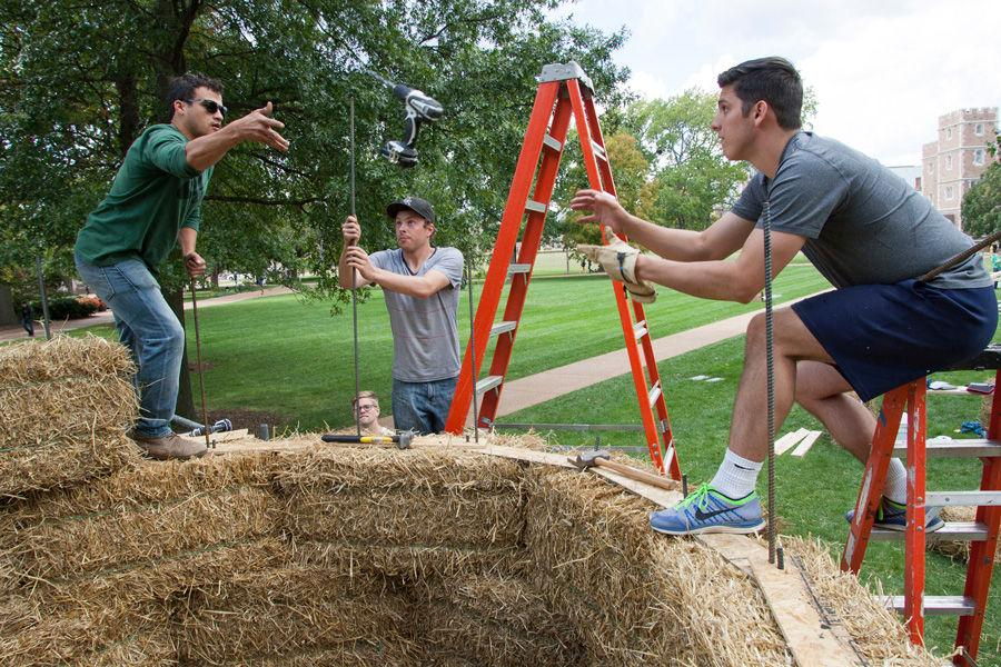 Working 7-feet up atop a sukkah made of hay bales, Devin Brown (left) tosses a cordless drill to Brandon Eversgerd as Eric Dernbach works on the rebar support structure. All are architecture students at Kansas State. The design (by Brown) was one 10 winners in the Sukkah City STL competition held by Washington University and St. Louis Hillel.