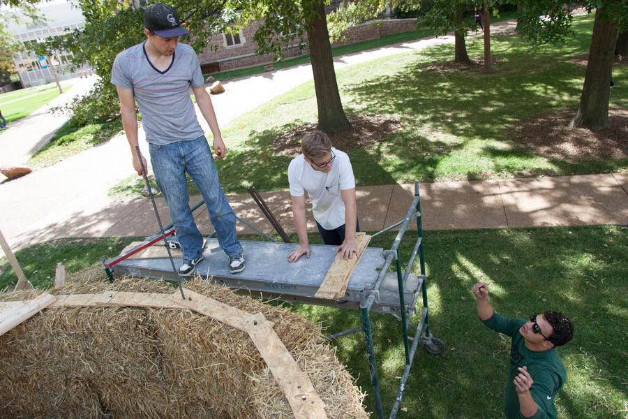 Kansas State architecture students Eric Dernbach (in baseball cap) and Andy McAllister work on constructing fellow student (in green shirt) Devin Brown's sukkah design on Oct. 6, 2014 at Washington University. Brown's design, made of hay bales, was one of 10 finalists in Sukkah City STL, held by St. Louis Hillel and Wash U. The teams constructed their sukkot on the quadrangle just west of the university's Olin Library.