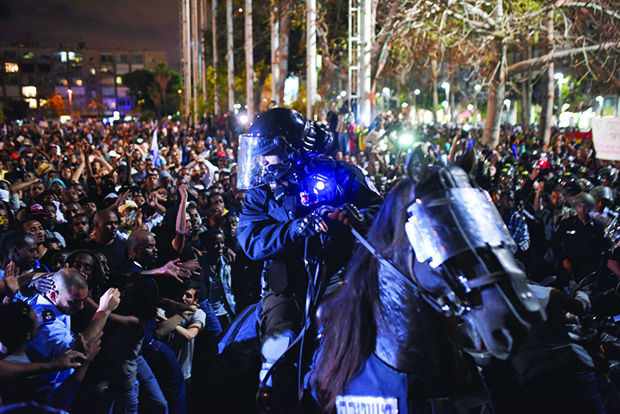 An+Israeli+policeman+tries%C2%A0to+disperse+the+hundreds+of+demonstrators+in+Tel+Aviv+protesting+on+behalf+of+Ethiopian-Israelis+on+May+3.+Photo%3A+Ben+Kelmer%2FFlash90