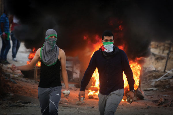 Palestinian protesters in the West Bank throwing stones and burning tires during clashes with Israeli security forces over the Al-Aqsa mosque compound, Sept. 30.Photo: Flash90