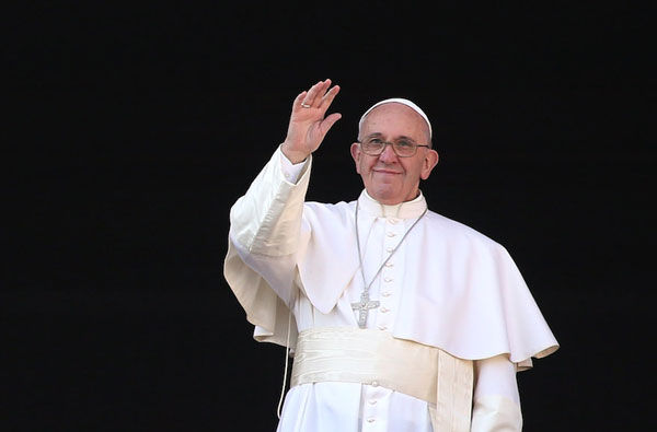 Pope+Francis+waving+from+the+balcony+of+St.+Peter%E2%80%99s+Basilica+in+Vatican+City%2C+Dec.+25%2C+2015.+%28Franco+Origlia%2FGetty+Images%29