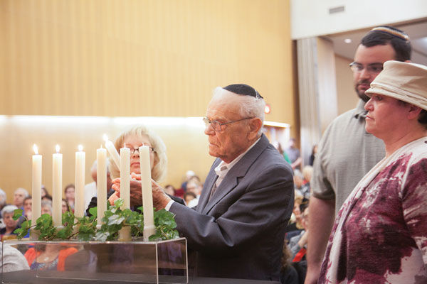 Benjamin Mkrtychyan lights a candle at last year's Yom HaShoah community commemoration.