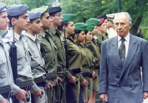 In November 1995, Israeli Defense Minister Shimon Peres reviews an honor guard at the Defense Ministry in Tel Aviv.
