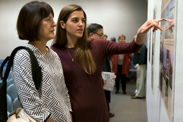 """First-year students from Washington University in St. Louis who were enrolled in the yearlong """"The History, Memory, and Representation of the Holocaust"""" program gathered at the Holocaust Museum and Learning Center for the Feb. 2 opening of an exhibit about their experiences. Above, student Cecily Hibbs tours the exhibit with her mother, Roz Hibbs. Photo: Sid Hastings / WUSTL Photos"""