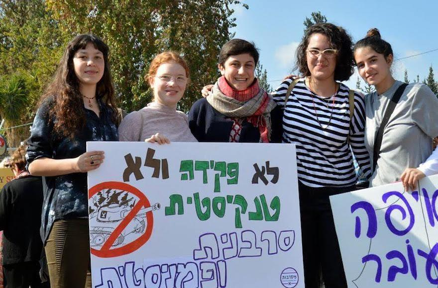 Tamar+Alon%2C+second+from+left%2C+and+Tamar+Zeevi%2C+center%2C+protesting+against+being+drafted+into+the+Israeli+army.+The+sign+reads%2C+%E2%80%9CNeither+clerks+nor+tank+drivers%2C+we+are+refusers+and+feminists.%E2%80%9D+%28Courtesy+of+Mesarvot%29