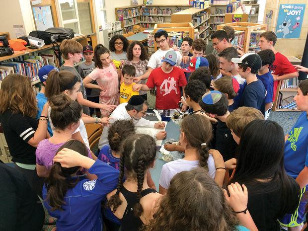 Jewish+Student+Union+director+Rabbi+Michael+Rovinsky+teaches+students+at+Saul+Mirowitz+Jewish+Community+School+on+Monday+about%C2%A0+inscribing%C2%A0letters+in+the+Torah.+JSU+received+funding+for+the+creation+of+a+Torah+for+community+youth+programs.%C2%A0