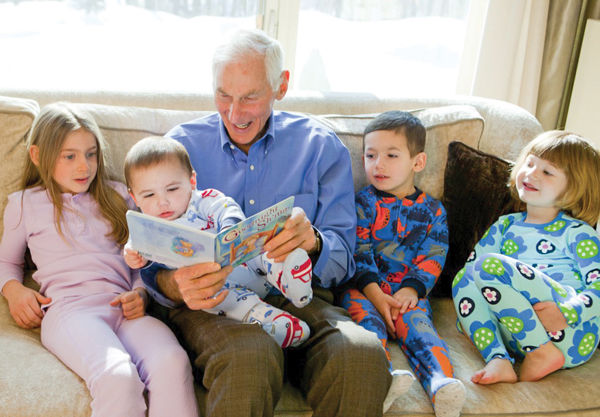 Harold Grinspoon, the founder of PJ Library, reads one of the program's books with a gaggle of children.