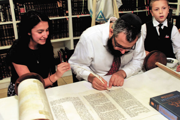Rabbi Hershey Novack and students such as junior Talia Menche had used a borrowed Torah before Chabad recently acquired one from Barnes-Jewish Hospital. Photo: Eric Berger