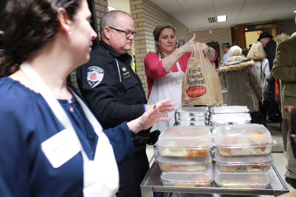 In this file photo, Jayme Fingerman (left) co-chaired Temple Israel's 2017 Thanksgiving Dinner for Those in Need and joined Creve Coeur police officers and volunteers such as Dee Mogerman in packing food for guests. Photos: Eric Berger