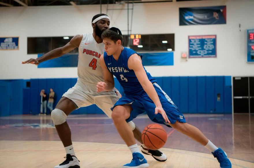 Sophomore+Gabriel+Leiter+of+the+Yeshiva+University+Maccabees+takes+on+a+player+from+Purchase+College+during+the+team%E2%80%99s+championship+victory+on+Feb.+25%2C+2018%2C+which+earned+an+automatic+qualification+into+the+NCAA+tournament.+%28Courtesy+Yeshiva+University%29