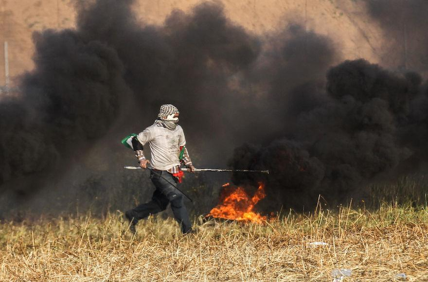 A+Palestinian+protester+burning+tires+during+clashes+with+Israeli+forces+near+the+border+of+the+southern+Gaza+Strip%2C+April+2%2C+2018.+Photo%3A+Said+Khatib%2FAFP%2FGetty+Images