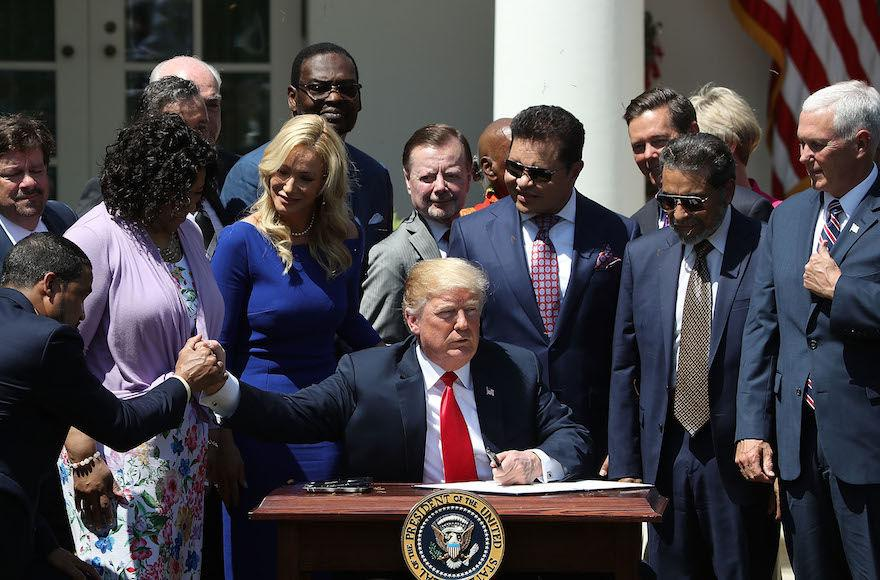 President+Donald+Trump%2C+flanked+by+members+of+faith-based+communities%2C+signs+a+proclamation+declaring+a+National+Day+of+Prayer+during+an+event+in+the+Rose+Garden+at+the+White+House%2C+May+3%2C+2018.+%28Mark+Wilson%2FGetty+Images%29%C2%A0
