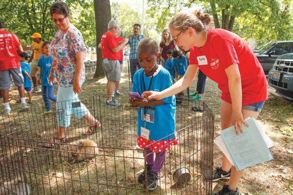 Volunteer Belle Gage, 14, of Central Reform Congregation, helps a camper take photos in the rabbit pen. Photo: Mike Sherwin