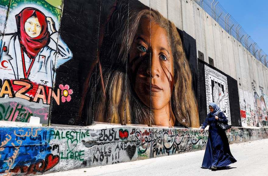 A+Palestinian+woman+walks+past+a+mural+of+Ahed+Tamimi+painted+on+Israel%E2%80%99s+separation+barrier+in+the+West+Bank+city+of+Bethlehem%2C+July+29%2C+2018.+%28Ahmad+Gharabli%2FAFP%2FGetty+Images%29