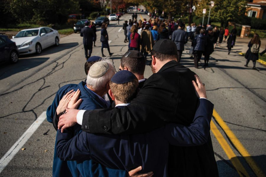 PITTSBURGH, PA - OCTOBER 31: Mourners embrace during a processional outside of Congregation Beth Shalom for the funeral of Joyce Fienberg who was killed at the mass shooting at the Tree of Life Synagogue on Wednesday, October 31, 2018, in Pittsburgh, PA. (Photo by Salwan Georges/The Washington Post via Getty Images)