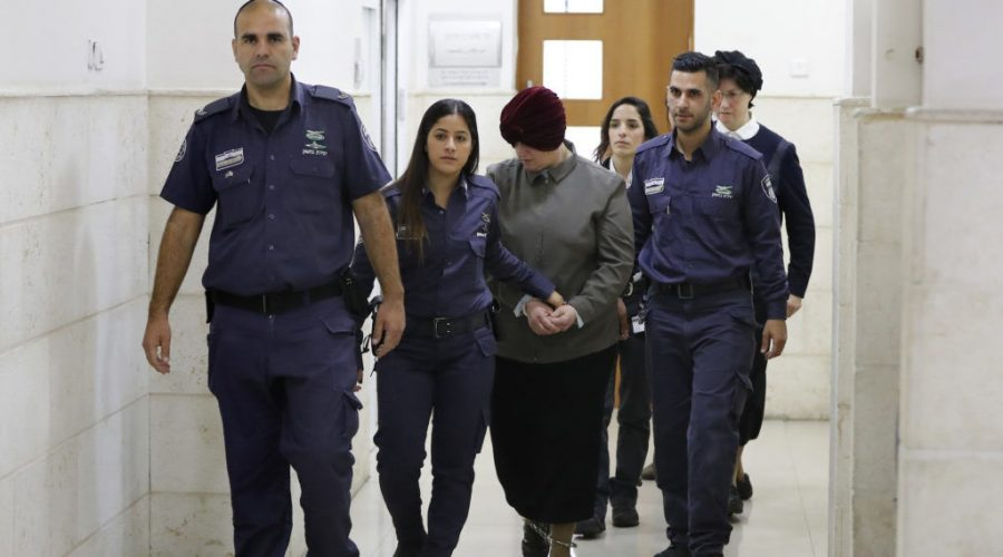 Malka+Leifer%2C+center%2C+a+former+Australian+teacher+accused+of+dozens+of+cases+of+sexual+abuse+of+girls+at+a+Melbourne+school%2C+is+escorted+by+police+as+she+arrives+for+a+hearing+at+the+District+Court+in+Jerusalem%2C+Feb.+27%2C+2018.+%28Ahmad+Gharabli%2FAFP%2FGetty+Images%29