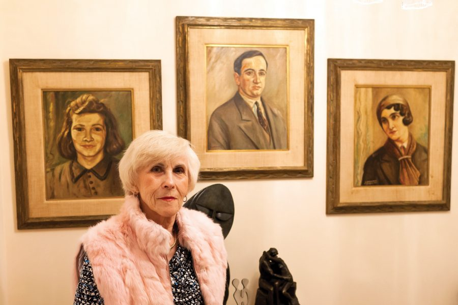 Rachel Miller at home, in front of paintings of three of her family members lost during the Holocaust— her mother, father and sister. A German prisoner of war created the portraits, working from photographs of the family. Photos: Lisa Mandel