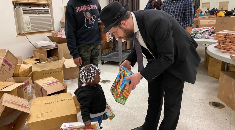 Rabbi+Moshe+Schapiro+shows+a+toy+to+a+child+during+the+charity+drive+in+Jersey+City%2C+N.J.%2C+Dec.+23%2C+2019.+%28Courtesy+of+Benny+Polatseck%29%C2%A0
