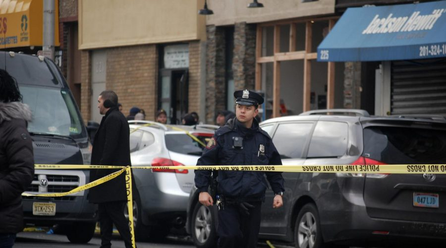 A police officer stands in front of the crime scene near JC Kosher Supermarket in Jersey City, N.J., the site of a deadly shooting, Dec. 11, 2019. (Laura E. Adkins/JTA)