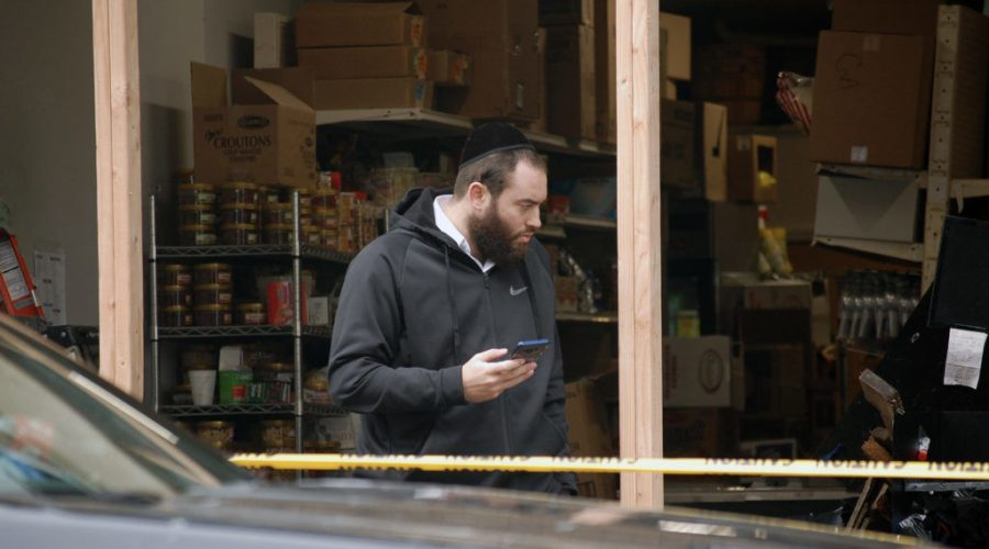A Hasidic man stands in front of JC Kosher Supermarket in Jersey City, N.J., the site of a shooting that left three dead along with the two shooters, Dec. 11, 2019. Police are still investigating whether it was a hate crime. (Laura E. Adkins/JTA News)