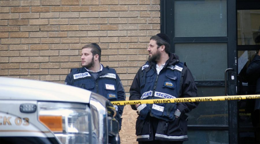 Hasidic members of Misaskim, which provides services for the care of the dead, stand in front of the K'hal Adas Greenville synagogue in Jersey City, N.J., next door to the JC Kosher Supermarket, the site of the deadly shooting that left three dead. Dec. 11, 2019. (Laura E. Adkins/JTA)
