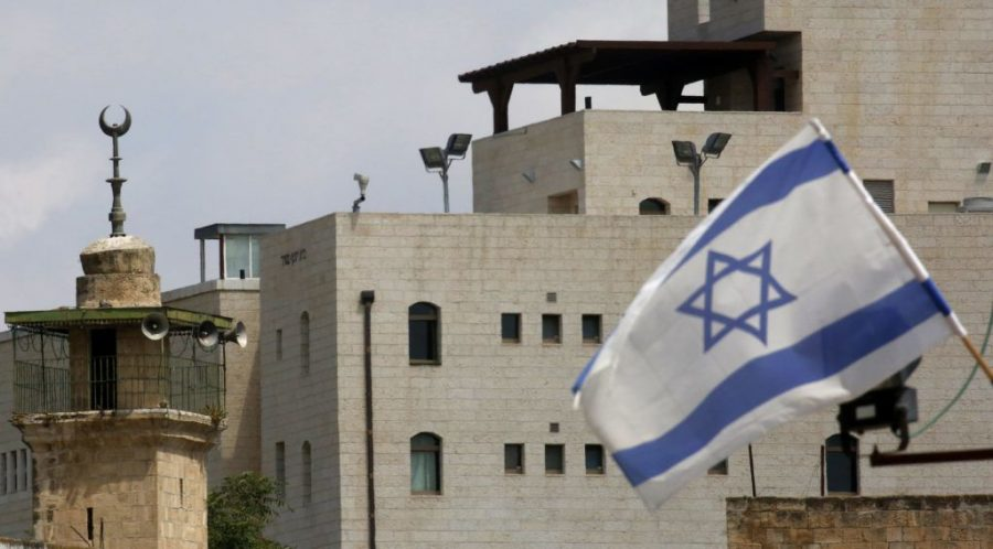 An+Israeli+flag+is+pictured+near+the+minaret+of+a+mosque+at+an+Israeli+settlement+in+Hebron%2C+June+14%2C+2019.+%28Hazem+Bader%2FAFP%2FGetty+Images%29