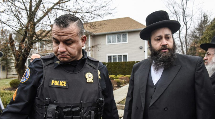 A+member+of+the+Ramapo+police+stands+guard+in+front+of+the+house+of+Rabbi+Chaim+Rottenberg+on+December+29%2C+2019+in+Monsey%2C+New+York.+Five+people+were+injured+in+a+knife+attack+during+a+Hanukkah+party.+%28Stephanie+Keith%2FGetty+Images%29
