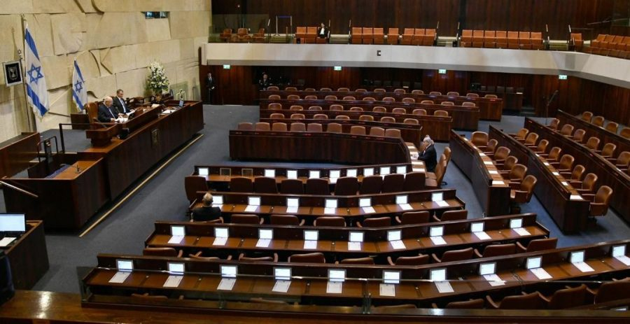 Israeli+President+Reuven+Rivlin%2C+flanked+by+Speaker+Yuli+Edelstein%2C+speaks+to+a+nearly+empty+Knesset+chamber%2C+where+only+Prime+Minister+Benjamin+Netanyahu+and+Blue+and+White+head+Benny+Gantz+are+seated+due+to+limits+to+protect+against+the+coronavirus+during+the+swearing-in+ceremony%2C+March+16%2C+2020.+%28Haim+Zach%2FGPO%29