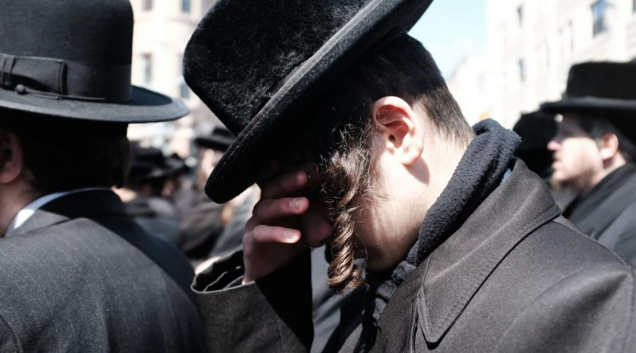 A+Hasidic+Jew+at+a+funeral+in+the+Brooklyn+neighborhood+of+Borough+Park+in+2019.+%28Spencer+Platt%2FGetty+Images%29
