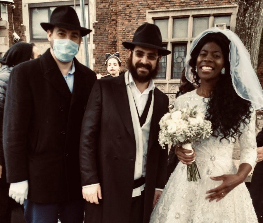 Alana+Cooper+and+her+husband%2C+Yisroel+Ygbi%2C+center%2C+at+their+wedding+in+Brooklyn.+%28Courtesy+of+Rabbi+Ari+Kirschenbaum%29