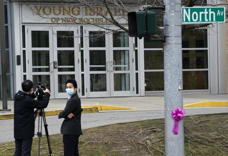 Members of the media wear protective masks film outside the Young Israel of New Rochelle, a suburban New York town at the center of a coronavirus outbreak in Westchester County, March 10, 2020. (Timothy A. Clary/AFP via Getty Images)