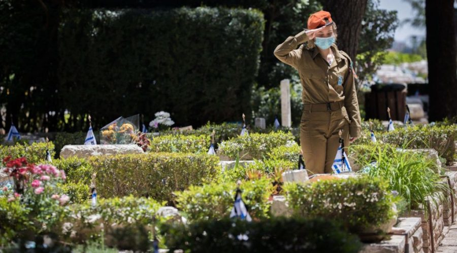 An+Israeli+soldier+places+flowers+on+the+graves+of+fallen+Israeli+soldiers+at+the+Mount+Herzl+military+cemetery+hours+before+the+start+of+Memorial+Day%2C+April+20%2C+2020.+%28Yonatan+Sindel%2FFlash90%29